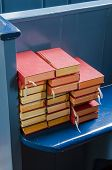 stock photo of pews  - Several red bibles on a blue pew in the church of Marken Netherlands - JPG