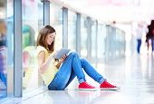 picture of mall  - Pretty young girl sitting on the floor in a shopping mall and using her tablet - JPG