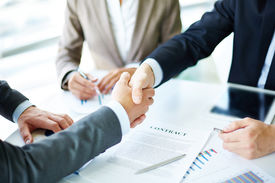 stock photo of handshake  - Image of business partners handshaking over business objects on workplace - JPG