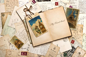 stock photo of vintage antique book  - old postcards letters mails and open journal with sample text My Travel Book - JPG