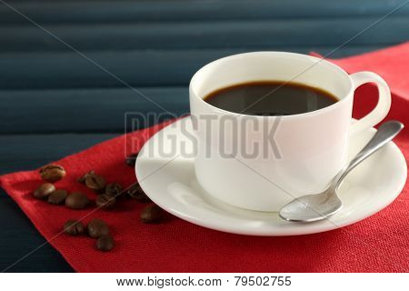 Cup of coffee on red napkin with coffee beans and spoon color wooden background