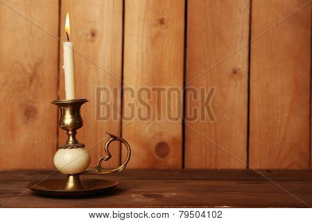 Retro candlestick with candle on wooden background