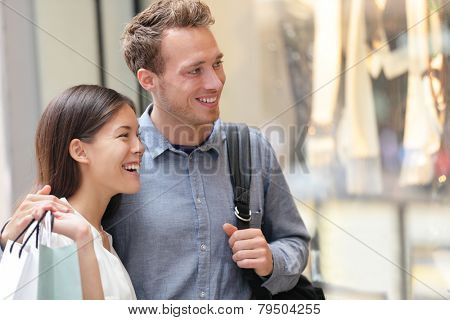 Couple shopping in Hong Kong Central looking at shop windows holding shopping bags. Urban mixed race Asian Chinese woman shopper and Caucasian man smiling happy living in city.