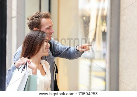 People shopping in Hong Kong Central. Couple looking at shop windows holding shopping bags. Urban mixed race Asian Chinese woman shopper and Caucasian man smiling happy living in city.