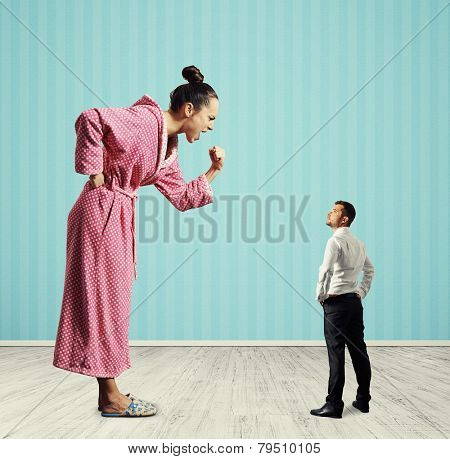 angry housewife screaming at her husband and showing fist