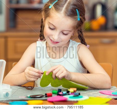 happy cute little girl is engaged in sewing  home