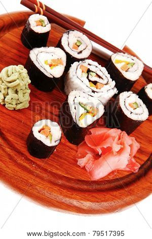 Japanese traditional Cuisine - Roll with Cucumber , Cream Cheese with raw Tuna(maguro) and Salmon(sake) inside. on wooden plate with wasabi and ginger isolated over white background