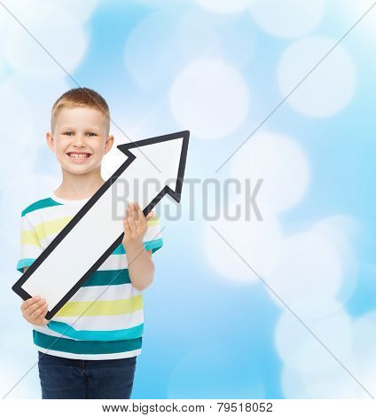 advertising, direction and childhood concept - smiling little boy with white blank arrow pointing up over blue background