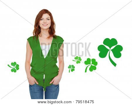 gestures, holidays, st. patricks day and people concept - happy teenager in green vest over white background with shamrock or clover