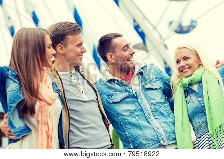 leisure, amusement park and friendship concept - group of smiling friends ferris wheel on the back