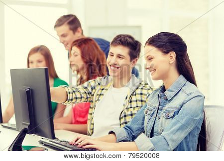 education, technology and school concept - smiling female student with classmates in computer class at school