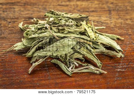 pile of stevia dried leaves against grunge wood -  natural sweetener, sugar substitute