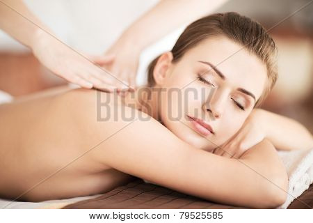 beauty and spa concept - beautiful woman in spa salon getting massage