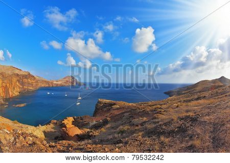 Quiet ocean cove on the island of Madeira. White yachts lit sunset. Calm on the Atlantic Ocean