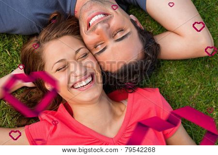 Two friends smiling while lying head to shoulder with an arm behind their head against hearts