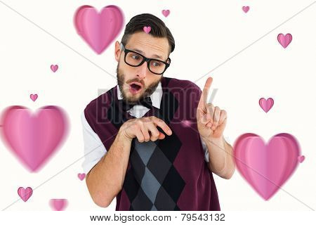 Geeky hipster in sweater vest pointing against hearts