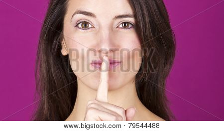 Portrait Of A Confident Beautiful Young Woman With A Finger On Her Lips