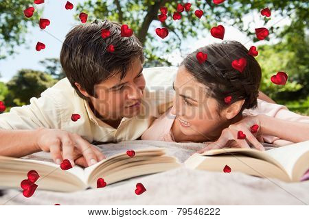 Two friends looking at each other while reading books on a blanket against valentines heart design