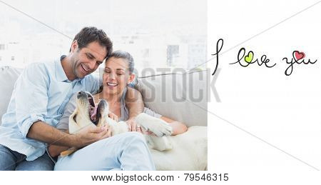 Happy couple petting their yellow labrador on the couch against i love you