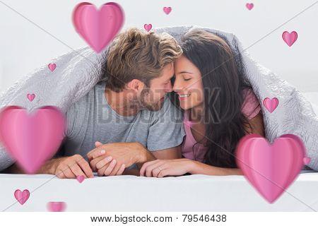 Cheerful couple head against head under the duvet against hearts