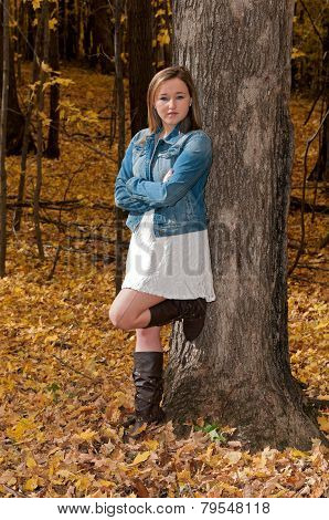 Young Female Arms Crossed Against Tree
