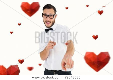 Geeky hipster pointing at camera against hearts