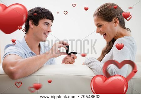 Man making a proposal to his girlfriend against love heart pattern