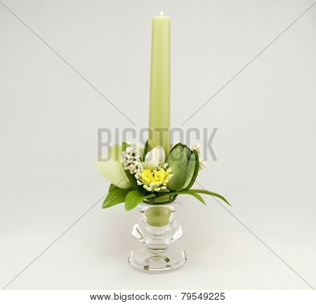 Candle holder with green pillar candle against gradient background