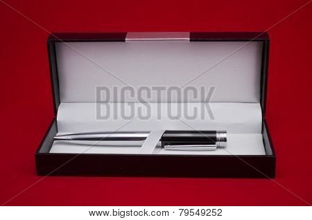 Metallic pen in a gift box against red background