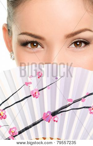 Asian eyes woman. Eye makeup asian look with paper fan. Beauty portrait of mixed race Asian / Caucasian female model on white background. Close up on eyes.