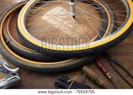 Bicycle repair. Repairing or changing a tire or wheel of an vintage bicycle. Old bicycle wheels on a grungy work desk with well used tools and bicycle parts.