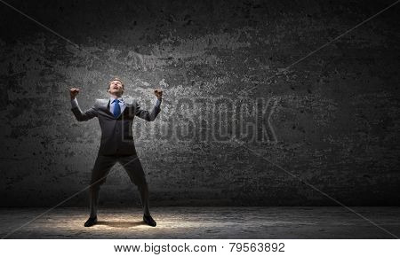 Young handsome businessman with hands up celebrating success