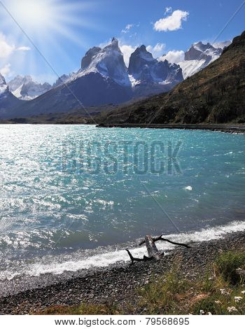 A strong wind blows turquoise waves on the lake, grand cliffs of Los Kuernos covered with snow and ice.  Magic beauty of Lake Pehoe
