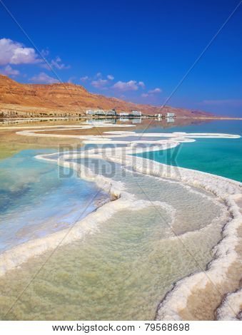 The path from salt picturesquely curls in salty water. Hotels are reflected in smooth water ashore. Israeli coast of the Dead Sea