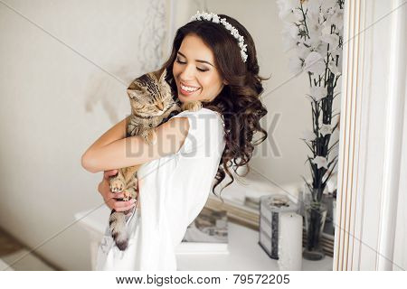 The woman in the bedroom with the cat in her arms.