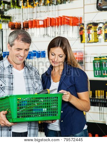 Couple carrying basket full of tools in hardware store