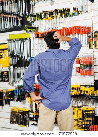 Rear view of confused customer scratching head in hardware shop