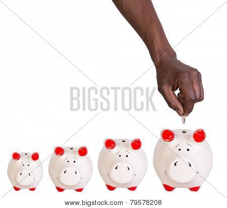 Male hand putting a coin into a piggy bank isolated on white background