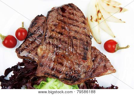meat food : two roast steak boneless with red and chili peppers, served on green lettuce salad on dish isolated over white background