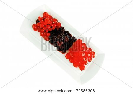 cherry and wild berrys over white dessert plate