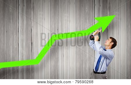 Young businessman using drill to fix growing arrow