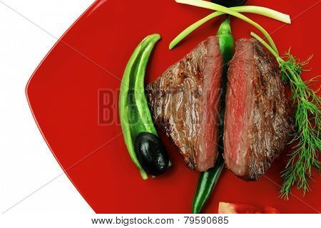 meat savory : grilled beef fillet mignon on red plate with tomatoes apples and pepper isolated over white background