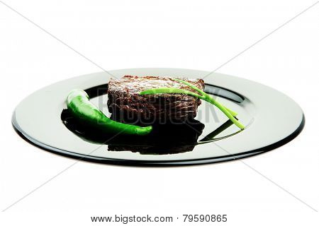 meat savory : grilled beef fillet mignon served on black plate isolated over white background with chili pepper