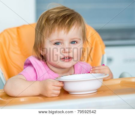 little girl in a highchair for feeding with a spoon and a plate in the kitchen