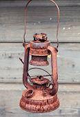 stock photo of kerosene lamp  - Old rusted red kerosene lamp on gray wooden wall background - JPG