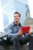 stock photo of late 20s  - Urban young professional man using tablet computer sitting in Hong Kong outside using app on 4g wireless device wearing headphones - JPG