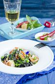 image of cuttlefish  - Pasta with cuttlefish ink and vegetables on wooden table  - JPG