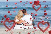 stock photo of couple sitting beach  - Affectionate couple sitting on the sand at the beach against love heart pattern - JPG