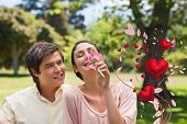 pic of she-male  - Man watching his friend while she is smelling a flower against valentines heart design - JPG