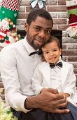 foto of new years baby  - Happy black father and baby boy cuddling by fireplace - JPG